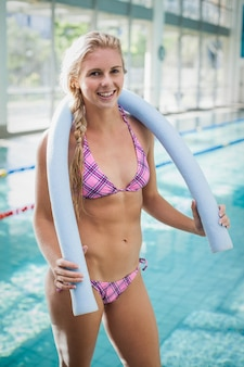 Attractive woman holding foam roll around her neck at the pool