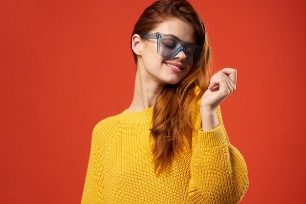 Привлекательная женщина, держащая волосы очки модный желтый свитер