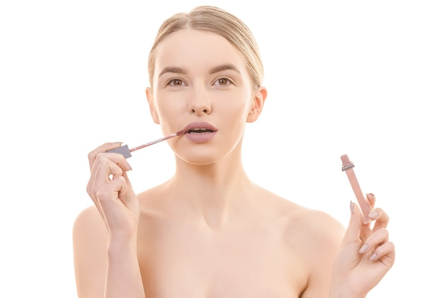 The attractive woman holding a lip gloss on the white background