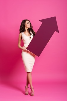 Attractive woman holding pink arrow sign