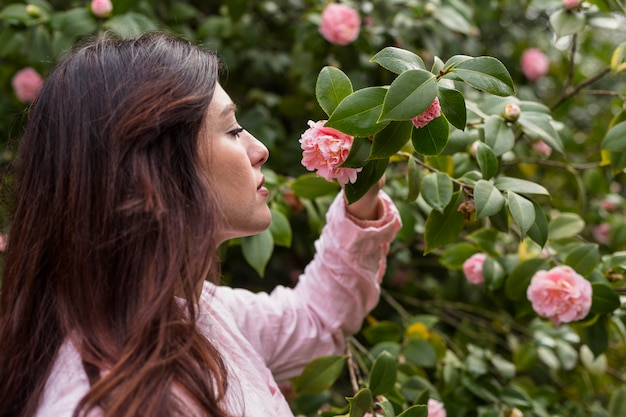 Attractive woman holding pink flower growing on green twig