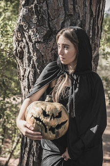 Attractive woman holding pumpkin, leaning on tree