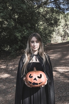 Attractive woman holding pumpkin in park