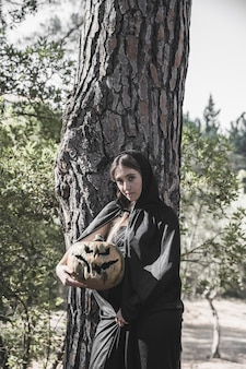 Attractive woman holding pumpkin and suit, leaning on tree
