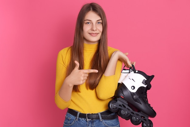 Attractive woman holding roller skating in hands and pointing at it with her index finger, , posing against rosy wall.