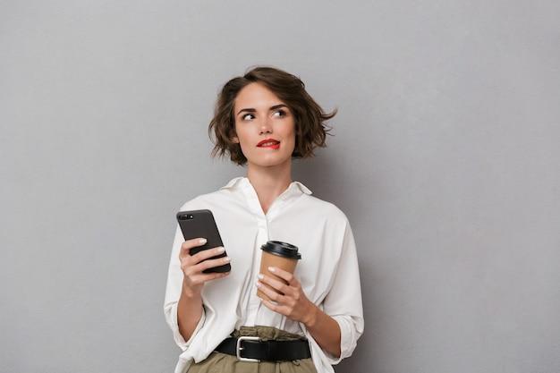 テイクアウトコーヒーを保持し、携帯電話を使用して、灰色の壁に隔離の魅力的な女性