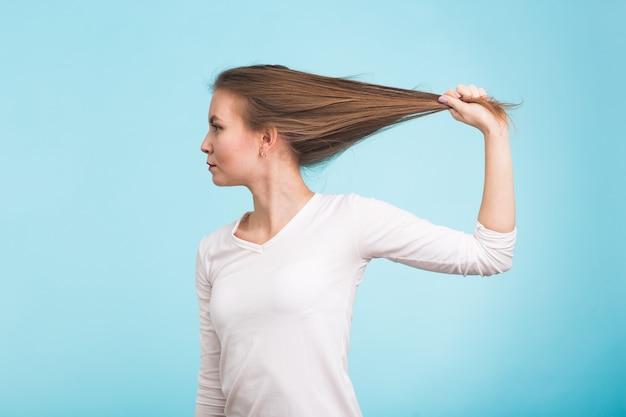 髪を抱えた魅力的な女性。青い背景に健康で強い髪。