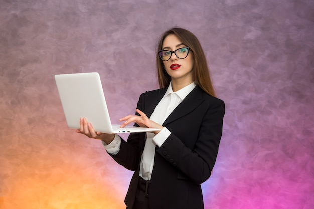 Attractive woman holding white laptop. secretary or student or teacher posing on abstract background