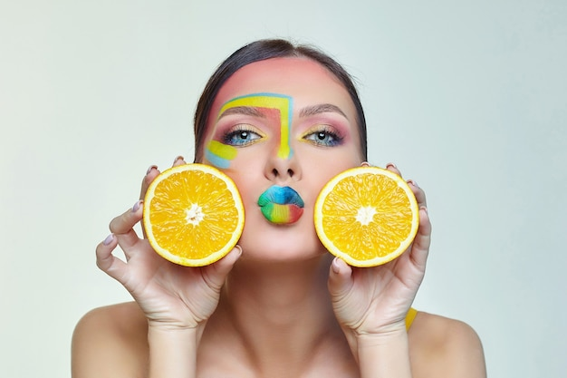 魅力的な女性は彼女の顔の前にオレンジスライスを保持します