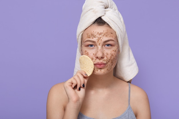 Attractive woman holds soft little sponge for facial treatments, stands wrapped in white towel, applies fresh clay mask for cleaning face