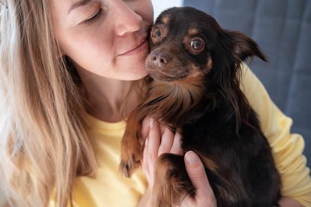 Привлекательный взгляд объятия женщины на смешной коричневый русский той терьер. концепция ухода за домашними животными.