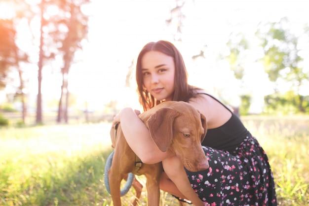 夕日の公園で美しい若い犬を抱いて魅力的な女性。犬に焦点を当てます。