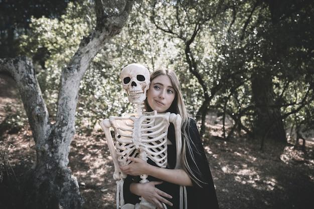 Привлекательная женщина, обнимающая за скелетом