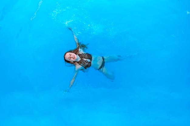 黒い水着姿の魅力的な女性がプールで背中に浮かび、コピースペースでリラックス。上からの眺め
