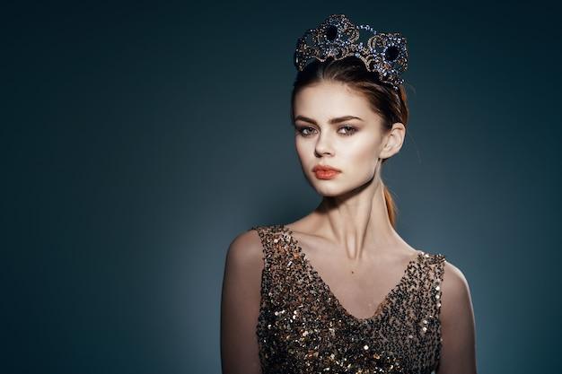 그녀의 머리 장식 스튜디오에 왕관과 함께 황금 드레스에 매력적인 여자