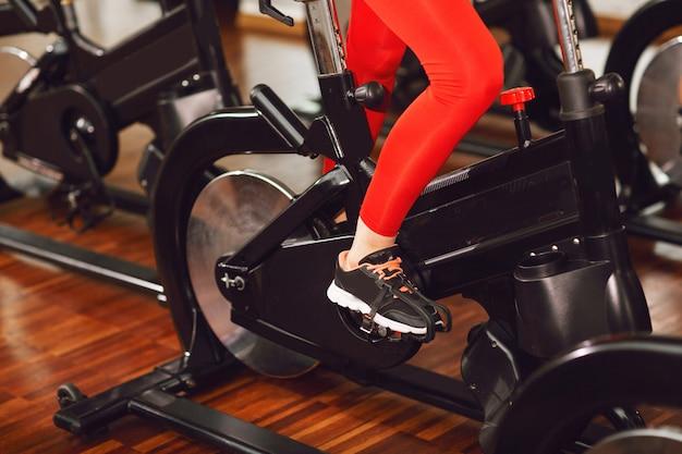 속도 고정식 자전거를 타고 체육관에서 빨간 스포츠 정장에서 매력적인 여자. 여자의 다리를 닫습니다.