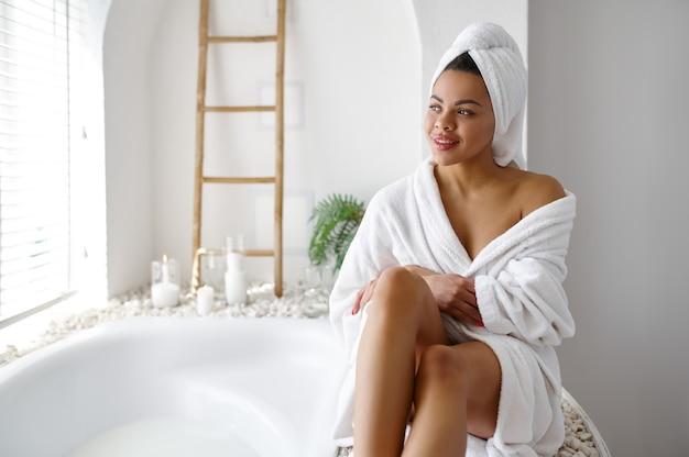 お風呂の近くに座っているバスローブの魅力的な女性。バスタブの女性、スパの美容とヘルスケア、バスルームのウェルネストリートメント、背景の小石とキャンドル
