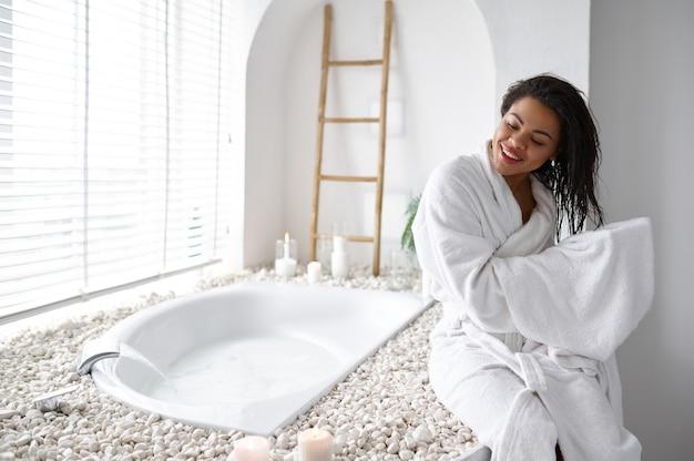 バスローブを着た魅力的な女性がお風呂の近くでタオルで髪を拭きます。バスタブの女性、スパの美容とヘルスケア、バスルームのウェルネストリートメント、背景の小石とキャンドル