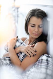 이불으로 자신을 덮고 침대에서 매력적인 여자
