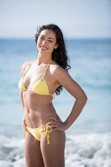 Привлекательная женщина в бикини, стоя на берегу моря