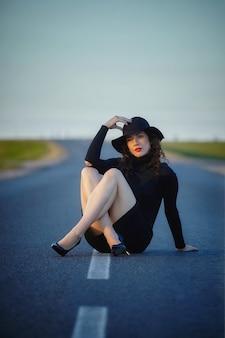 黒のドレスと帽子の分割ストリップが付いている道でポーズで魅力的な女性