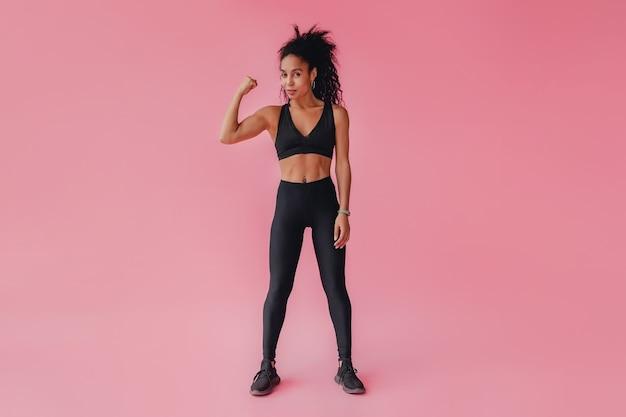ピンクの孤立した壁に黒いレギンスとトップフィットネス衣装の魅力的な女性
