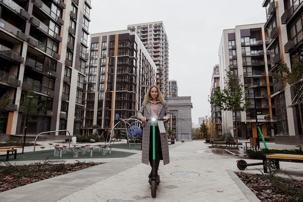 カジュアルな服装の魅力的な女性は、レンタルの電動スクーターに乗ります。背景のアパートのブロック。街を旅する快適な方法。高速旅行のコンセプト。エコ習慣。
