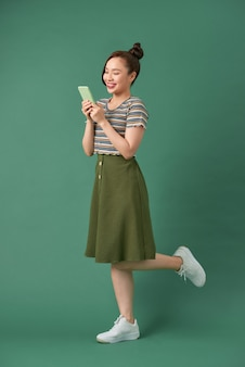 緑の上に携帯電話を使用してカジュアルな服装で魅力的な女性