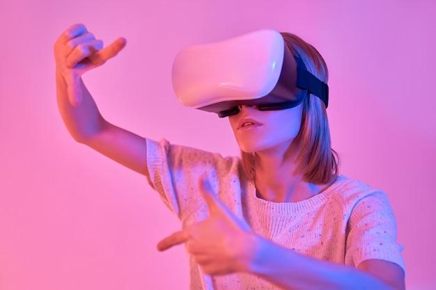 가상 현실 안경을 사용하여 캐주얼에 매력적인 여자, 네온 핑크에 고립 된 손 제스처 프레임