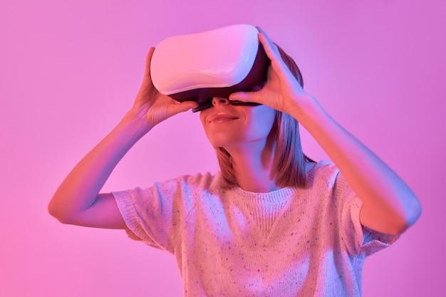 네온 핑크에 고립 된 가상 현실 안경을 사용하여 캐주얼에 매력적인 여자