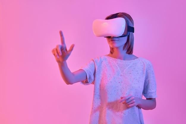 가상 현실 안경을 사용하는 캐주얼웨어에 매력적인 여자가 네온 핑크에 고립 된 그녀의 손가락으로 가상 버튼을 누르면