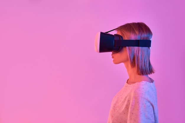 가상 현실 안경을 사용하여 캐주얼에 매력적인 여자, 네온 핑크에 고립 된 측면보기