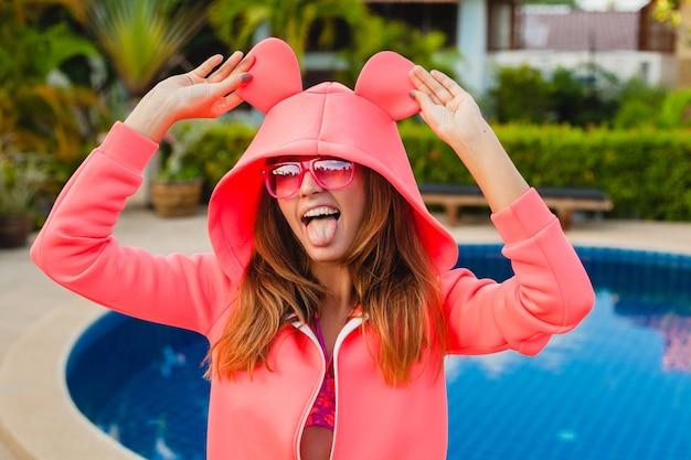 夏休みにサングラスをかけているカラフルなピンクのパーカーの魅力的な女性は、楽しい、スポーツファッションスタイルを持っている感情的な表情を笑顔