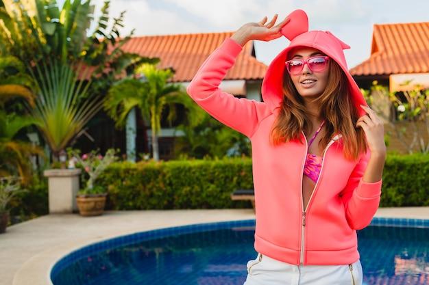 Привлекательная женщина в красочной розовой толстовке с капюшоном в солнцезащитных очках на летних каникулах, улыбаясь эмоциональным выражением лица, весело, спортивный стиль моды