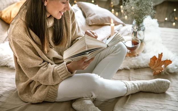 居心地の良い家庭服を着た魅力的な女性が本を読んでいます。秋の家の快適さ。