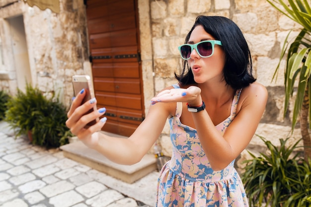 イタリアの旧市街中心部で休暇中にトレベリングドレスを着た魅力的な女性がキスを送信する電話で自分撮り面白い写真を作る
