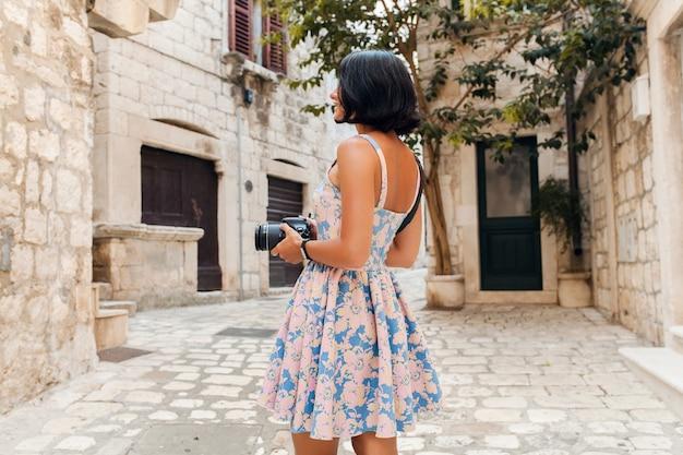 카메라에 사진을 찍는 이탈리아의 오래 된 도시 중심에서 휴가 트레블 드레스에 매력적인 여자
