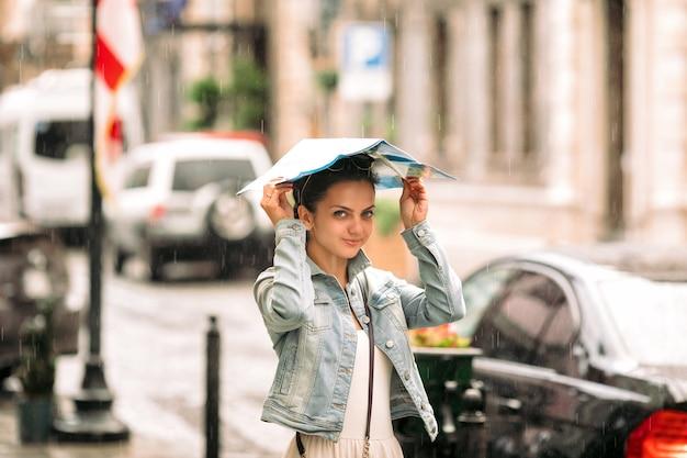 地図とドレスを着た魅力的な女性は雨の日に旧市街の通りを歩きます