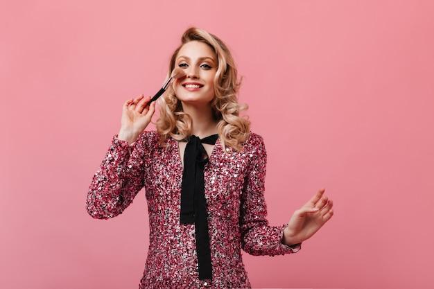 エレガントなドレスの魅力的な女性はピンクの壁に化粧をします