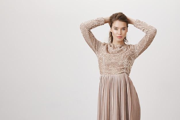 髪をとかすイブニングドレスの魅力的な女性