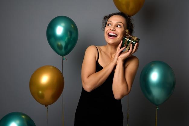 이브닝 드레스를 입은 매력적인 여성은 얼굴 근처에 크리스마스 선물을 들고 부드럽게 포옹하고 금색 녹색 공기 풍선이 있는 회색 배경의 복사 공간을 올려다봅니다. 새해, 광고에 대한 생일 파티 개념