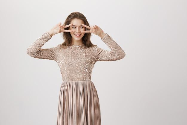 イブニングドレスの魅力的な女性は離れて見て、笑みを浮かべて