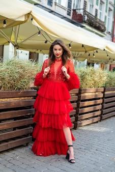 Привлекательная женщина в красном платье моды позирует на камеру на фоне городских.