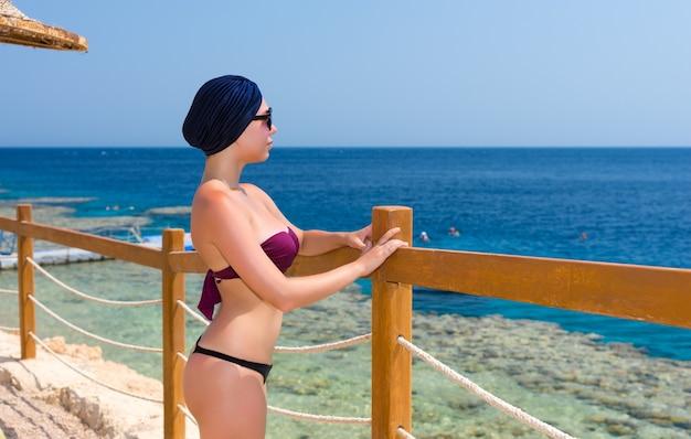 Привлекательная женщина в женском тюрбане и солнцезащитных очках стоит перед деревянным забором с веревочными вставками на пляже и смотрит на красивое море