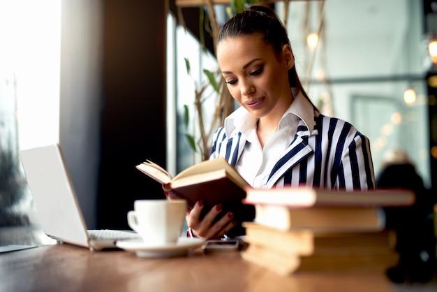 カフェで本を読んでフォーマルな服装で魅力的な女性
