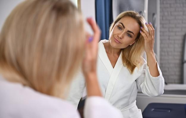 鏡の前で顔を見て、手で髪を触る魅力的な女性。バスルームでの美容写真、衛生、ボディケアのコンセプト