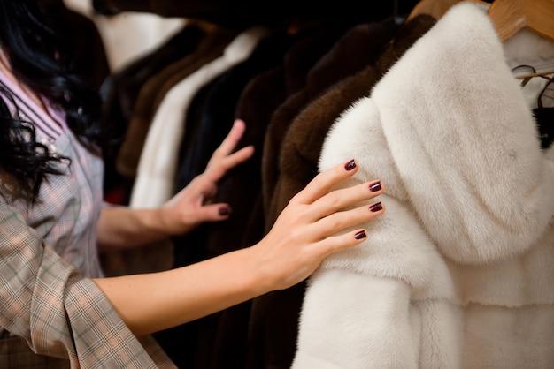 옷걸이에 모피 코트와 모피 코트 가게에서 매력적인 여자