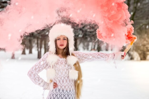 赤い煙に囲まれた毛皮の帽子の魅力的な女性