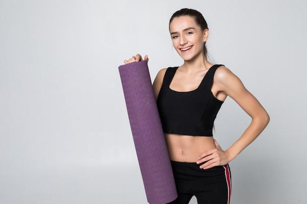 흰 벽에 고립 된 그녀의 뻗은 팔에 매트를 들고 체육관 복장에 매력적인 여자
