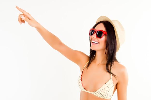 Привлекательная женщина в шляпе, бикини и очках указывая